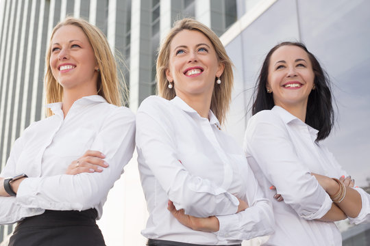 Three successful women with crossed hands standing and smiling