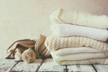 Stack of white cozy knitted sweaters on a wooden table.