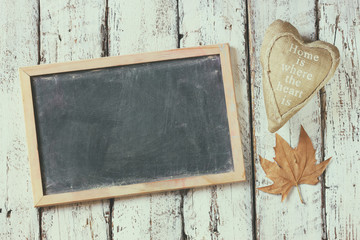 top view image of autumn leaves and fabric heart next to chalkboard over wooden textured background. copy space