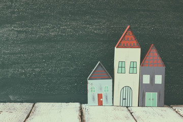 image of vintage wooden colorful houses decoration on wooden table  in front of  blackboard. faded retro filtered image