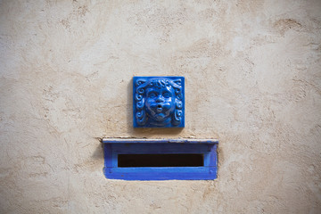 Plaster wall with blue decorative letter slot mailbox
