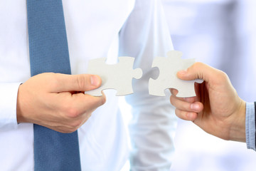 Close-up Of Businessmen Hand Connecting Jigsaw Puzzle