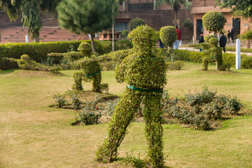 Topiary hedge figures depicting British soldiers firing rifles at the site of the Jallianwala Bagh massacre in Amritsar, India.