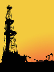 Silhouette of drilling rig on the oil&gas field with mountains and sunset