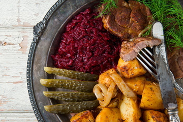 Roast Pork shoulder with Potatoes and salad from beetroot and pickled cucumbers