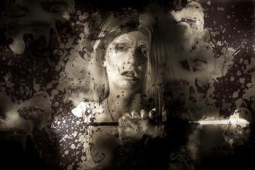 Evil vampire woman looking into bloody mirror