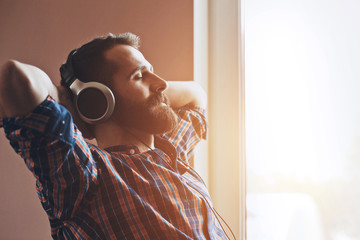 handsome bearded man  in headphones listening to music
