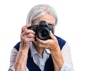 Senior woman shooting with a digital camera over white background