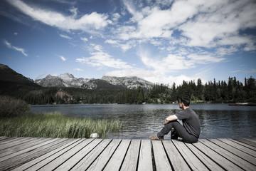 Man sitting on the bank of alpine mountain lake