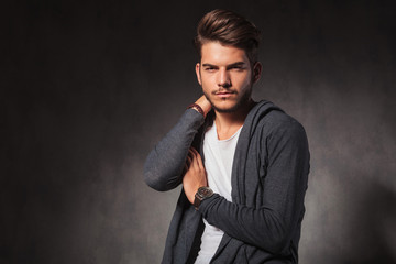 young man touching his shoulder while posing in studio
