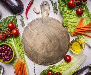 cutting board with a spread out around vegetables, beans, tomatoes, lettuce place for text, frame on wooden rustic background top view close up