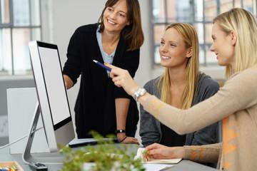 geschäftsfrau zeigt ihren kollegen etwas am computer