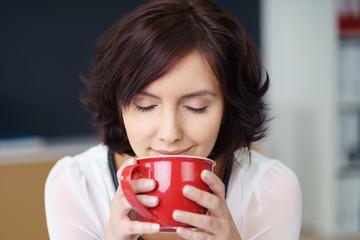 frau genießt eine tasse kaffee mit geschlossenen augen