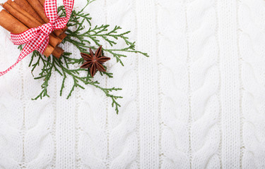 Christmas spices,anise and cinnamon on a knitted white background,texture of natural fibers.