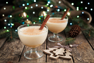 Eggnog traditional xmas homemade winter egg, milk, rum, vanilla alcohol liqueur preparation recipe in two glass cups with cinnamon sticks on wooden vintage table. Blue and green bokeh background