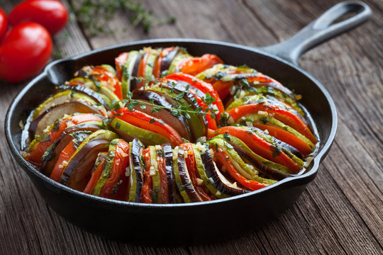 Traditional homemade vegetable ratatouille baked in cast iron frying pan healthy diet french vegetarian food on vintage wooden table background