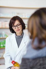apothekerin und kundin schauen auf ein arzneimittel