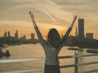 Happy woman raising her arms at sunrise in London