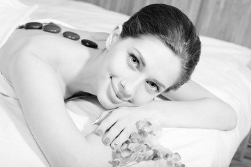 Portrait of sexy young pretty lady happy smile during spa procedures stone therapy massage and aromatherapy on white bed background