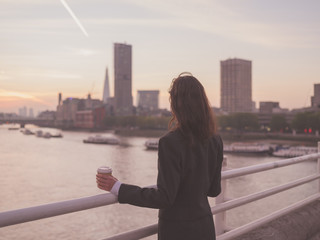 Businesswoman with cup admiring sunrise in London