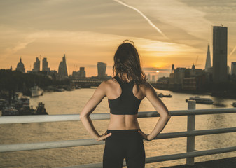 Athletic young woman on bridge at sunrise