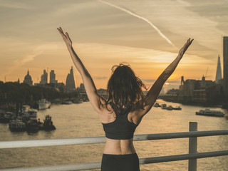 Happy athletic young woman wih arms raised at sunrise
