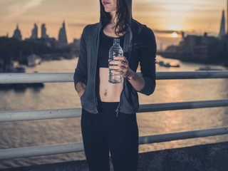 Fit young woman with bottle in city at sunrise
