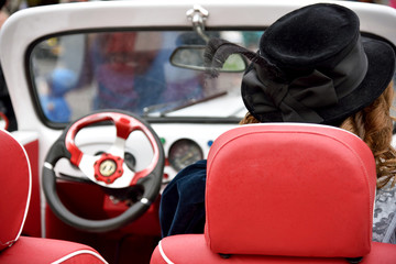 Curly girl in medieval dress and hat with feathers in retro car.