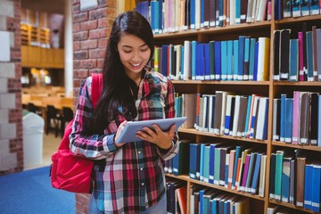 Smiling student in library using tablet