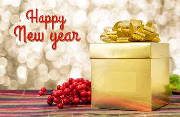 Happy new year word with Gold present box and ribbon on table wi