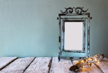 low key image of old victorian steel blue blank frame next to log tree with fairy christmas lights on wooden table