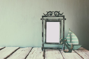 low key image of old victorian steel blue blank frame and wooden sailing boat on wooden table