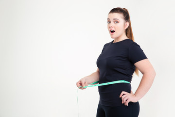 Fat woman measuring her waist and looking at camera