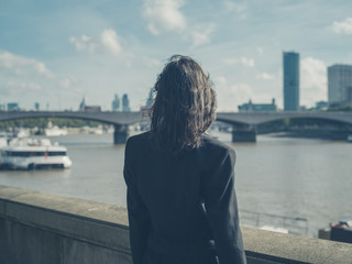 Rear view of businesswoman by river in city
