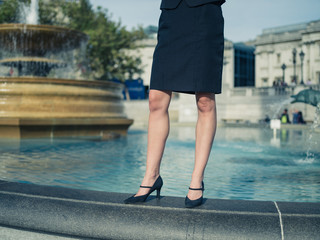 Young businesswoman standing by a fountain in the city