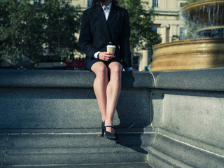 Young businesswoman with coffee by fountain