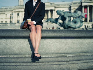 Young businesswoman sitting by fountain in city