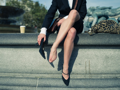 Businesswoman taking off her shoe in the city