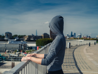 Young woman in hoodie by fene in city