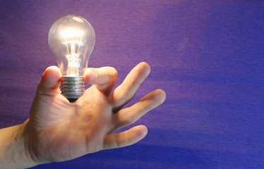Lighting lamp flashing bulb in human hand on blue background new idea