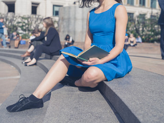 Young woman reading in the city
