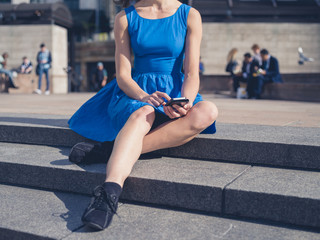 Young woman using her smart phone in the city