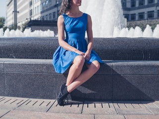 Young woman sitting by fountain in city