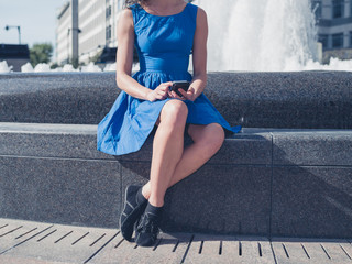 Young woman using smart phone by fountain in city