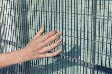 Female hand grabbing wired fence