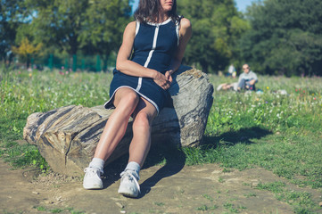 Young woman relaxing on log in park