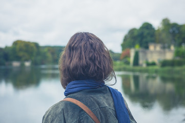 Young woman by lake in formal garden