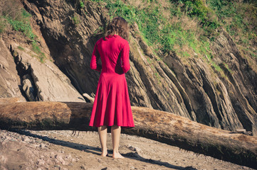 Woman in red standing on the beach