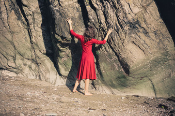 Young woman in red dress touching rock