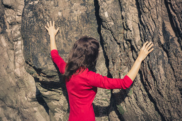 Woman in red dress touching rock wall